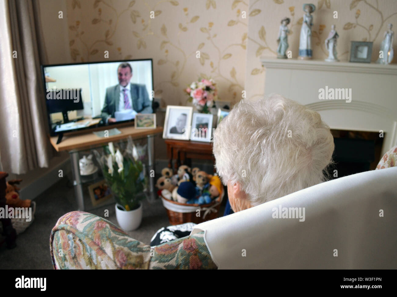 London, UK. 09th July, 2019. 93-year-old Irene sits in her living room in front of the television. In Great Britain, there is a heated debate about the recent decision of the BBC to re-invest over 75-year-olds in radio licence fees. From June 2020, they will also have to pay the 154.50 pounds (equivalent to around 172 euros) annually. Since 1999, senior citizens have been excluded. Credit: Christoph Meyer/dpa/Alamy Live News Stock Photo