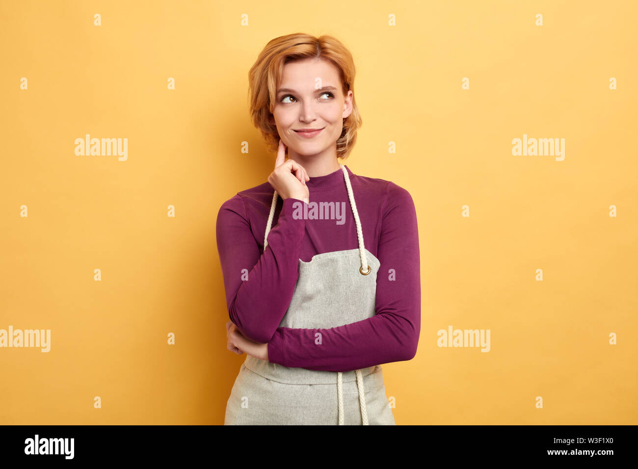 cunning housewife with a finger on her chin looking up thinking about her business, isolated yellow background, studio shot, copy space. idea, plan, - Stock Image