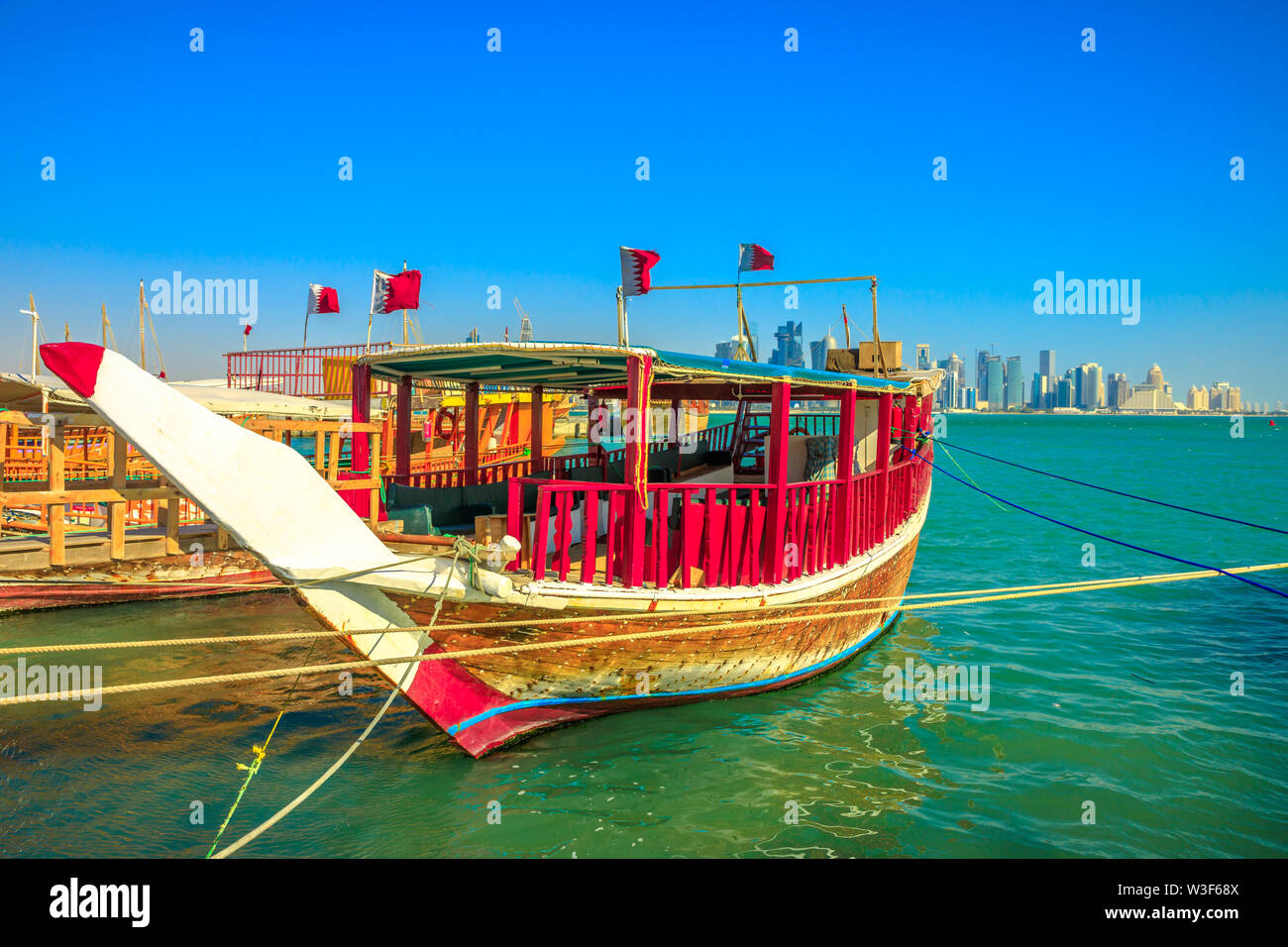 Perspective view of a traditional wooden dhow with qatari flag in foreground with seafront of Doha Bay and skyscrapers of West Bay skyline. Capital of Stock Photo