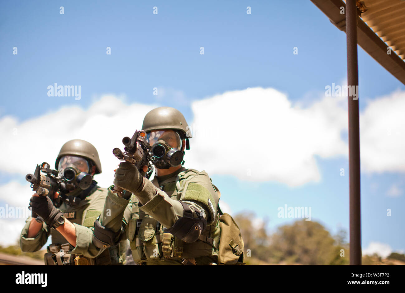Two police officers point a gun towards a target during an exercise at a training facility. - Stock Image
