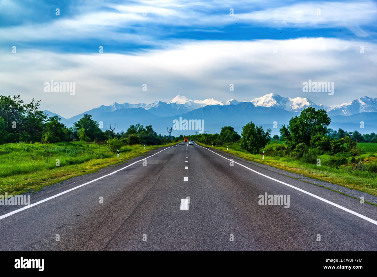 North Ossetia Republic, Russia - June 2019: Landscape with a road passing through the picturesque gorge and snow-capped peaks in the background. Fiagd - Stock Image
