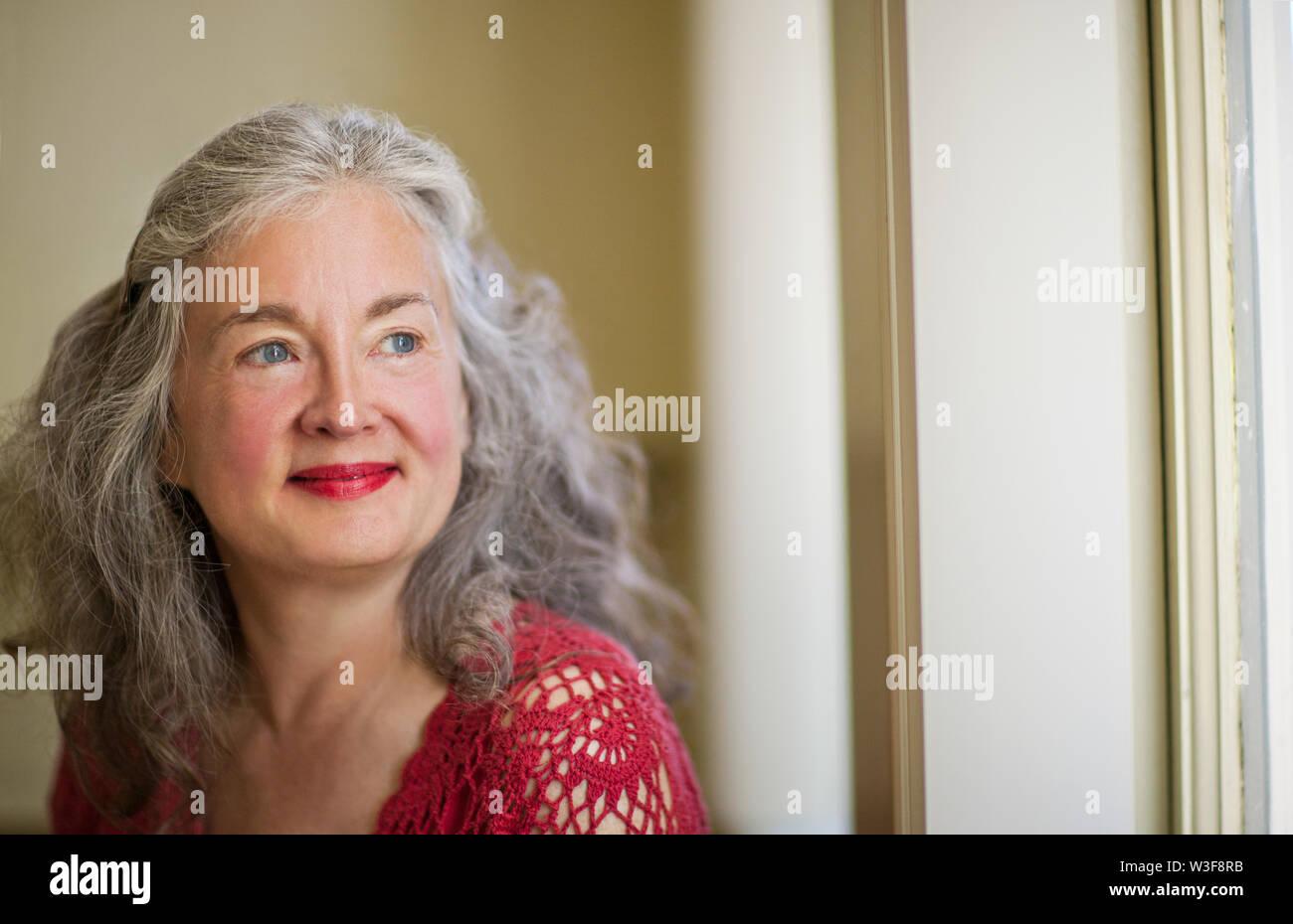 Smiling senior woman wearing red lipstick. - Stock Image