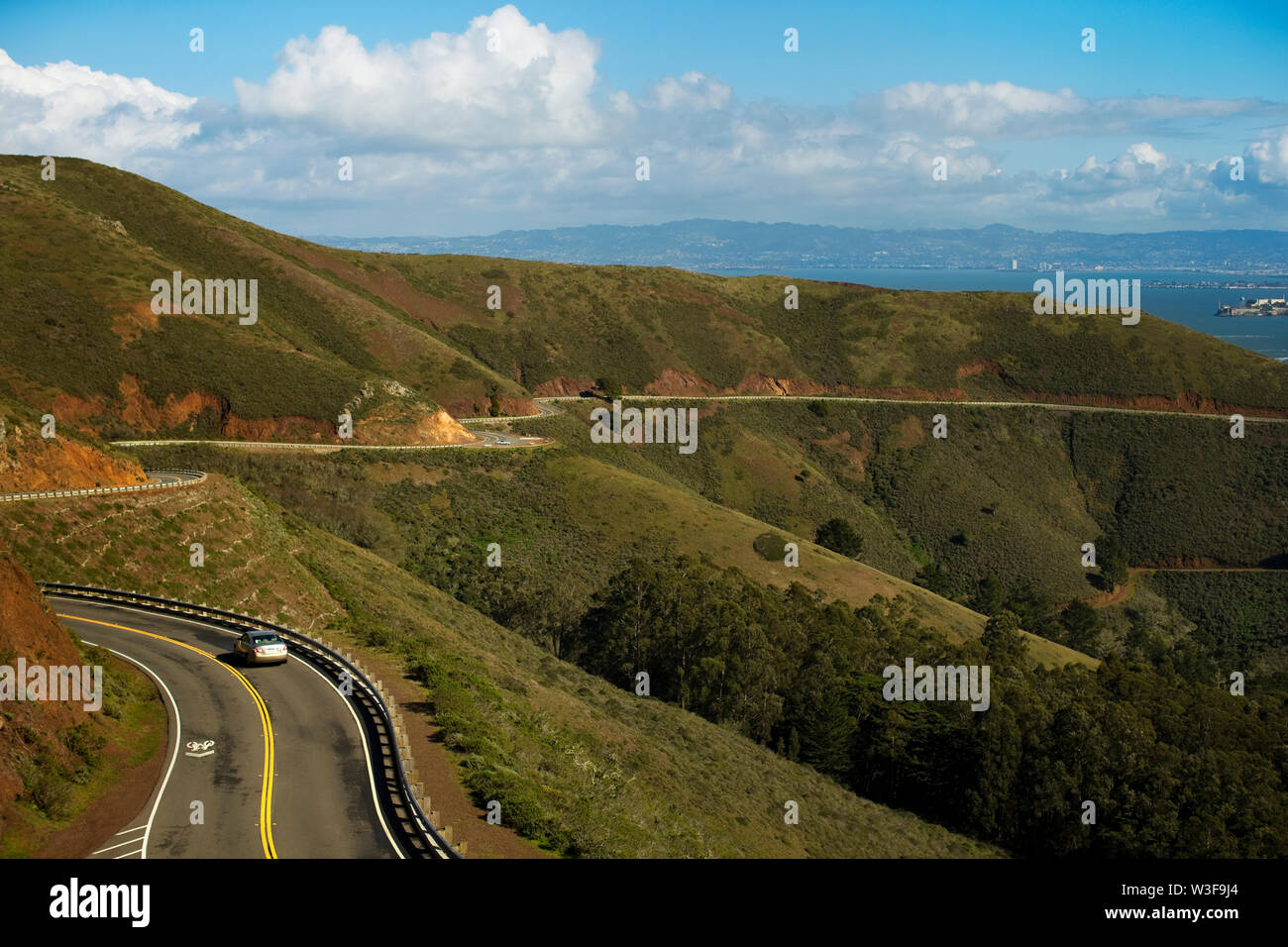 Car travelling on a winding road through a rural landscape. - Stock Image