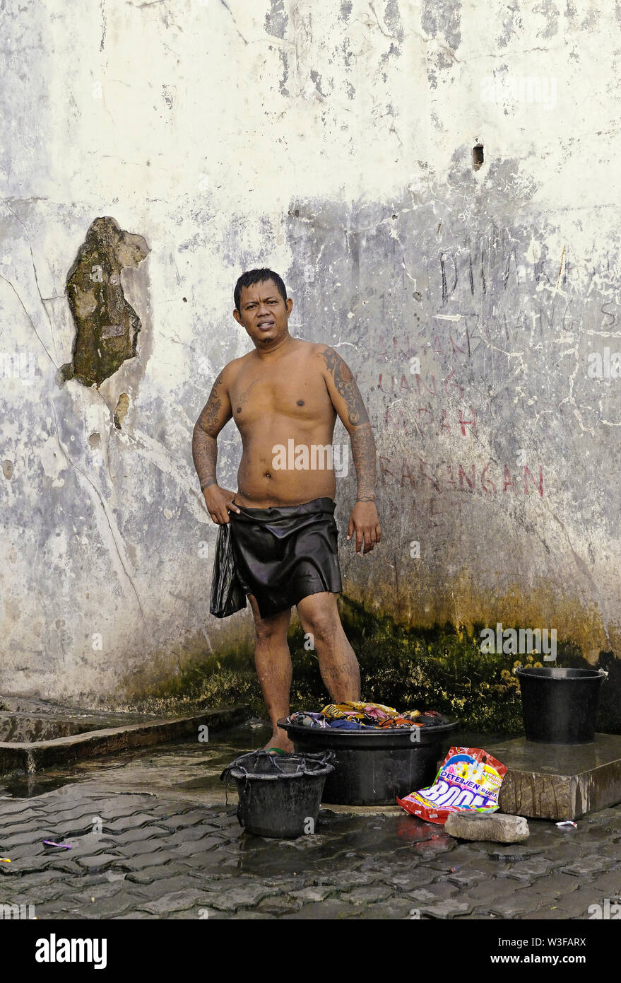 jakarta, dki jakarta/indonesia - may 28, 2010: a homeless construction migrant worker  washing himself and his clothes on jalan kunir in kota tua earl - Stock Image