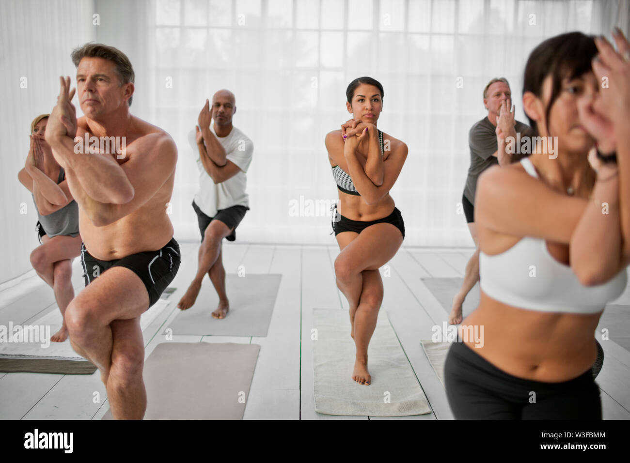 People practising the eagle pose during a yoga class. - Stock Image