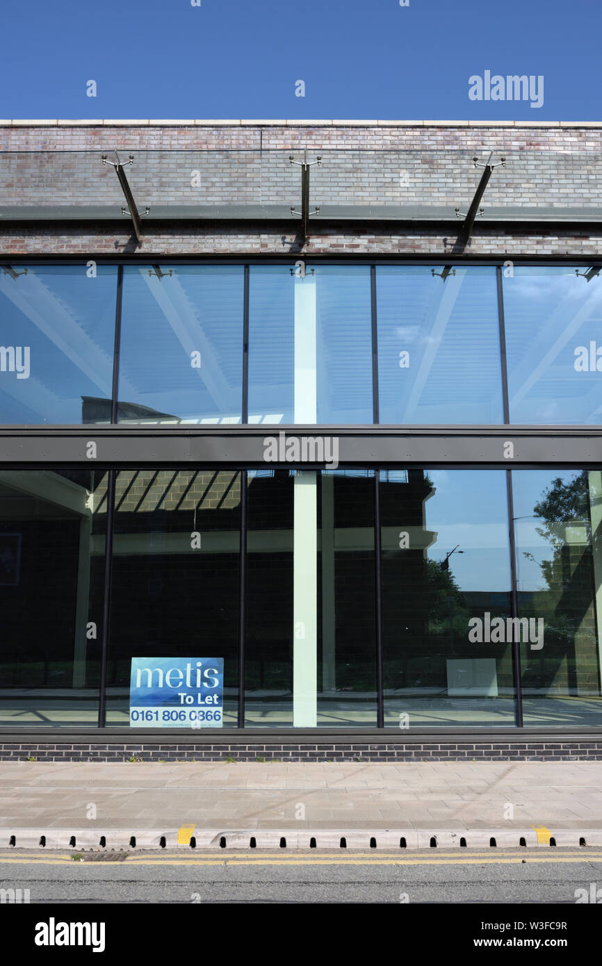 Glass curtain wall and cantilevered glass canopy on empty, to let, commercial building in bury lancashire uk Stock Photo