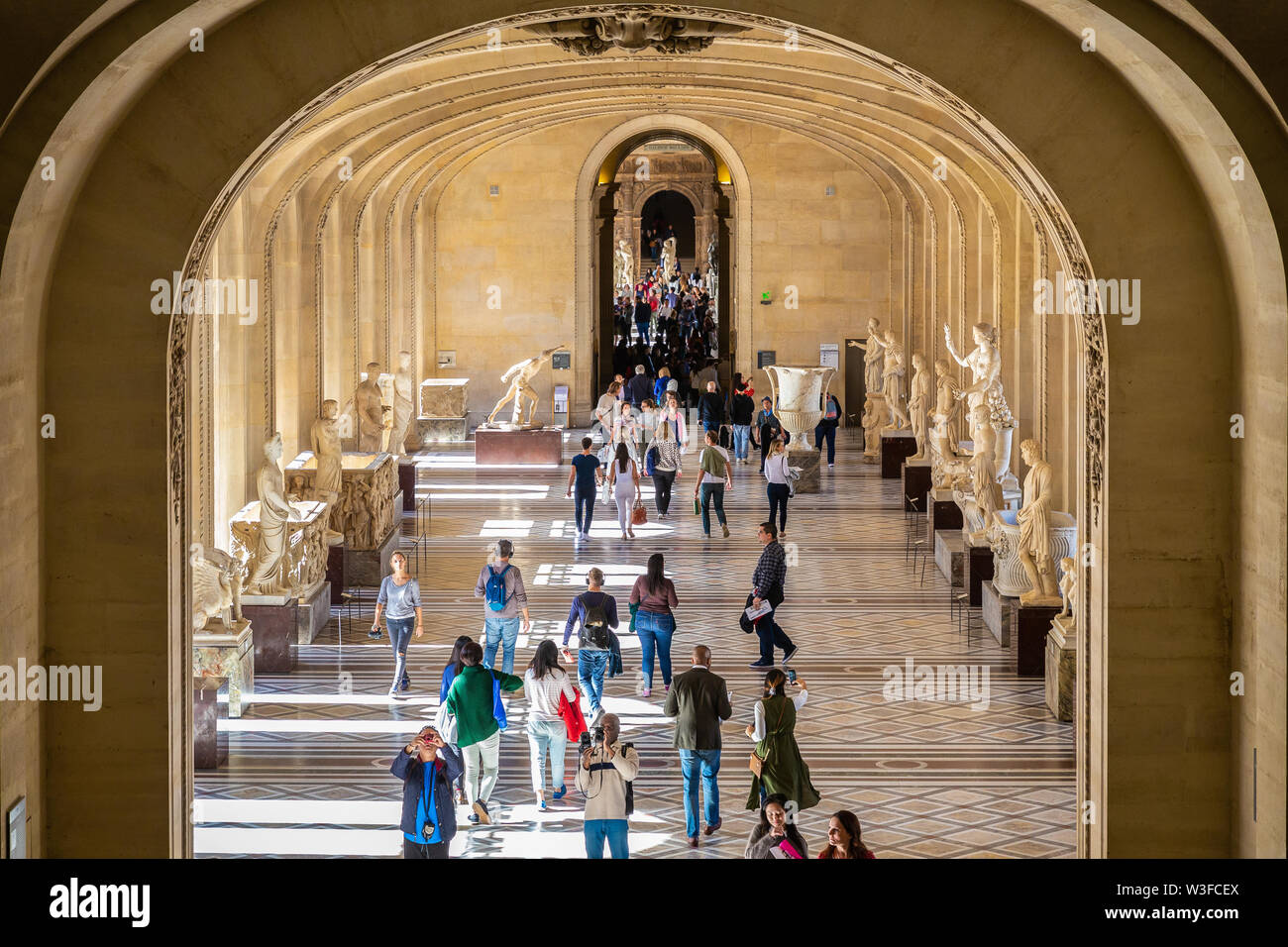 Paris, France - September 30, 2018: Looking through a big gate to tourists walking on passage surrounding by exhibition of old sculptures inside Louvr - Stock Image