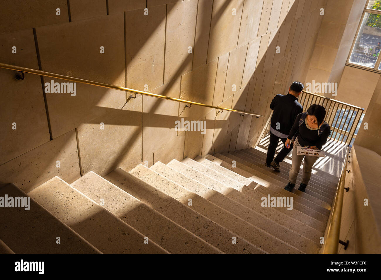Paris, France - September 30, 2018: Man and Woman walking on old mable stair brighten up by sunlight from windows. - Stock Image