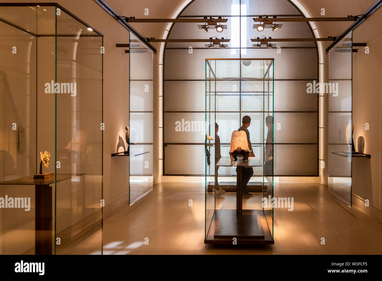 Paris, France - September 30, 2018: Tourist walking inside a glass room showing ancient items inside Louvre museum. - Stock Image