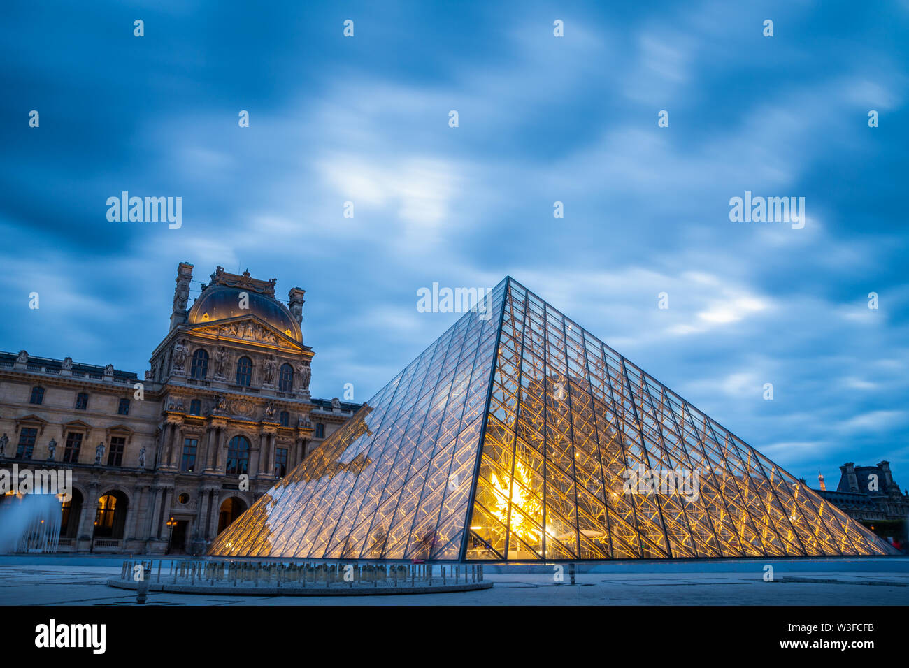 Paris, France - September 30, 2018: Iconic glass pyramid of Louvre museum with blurry motion of blue cloudy sky at sunset. - Stock Image