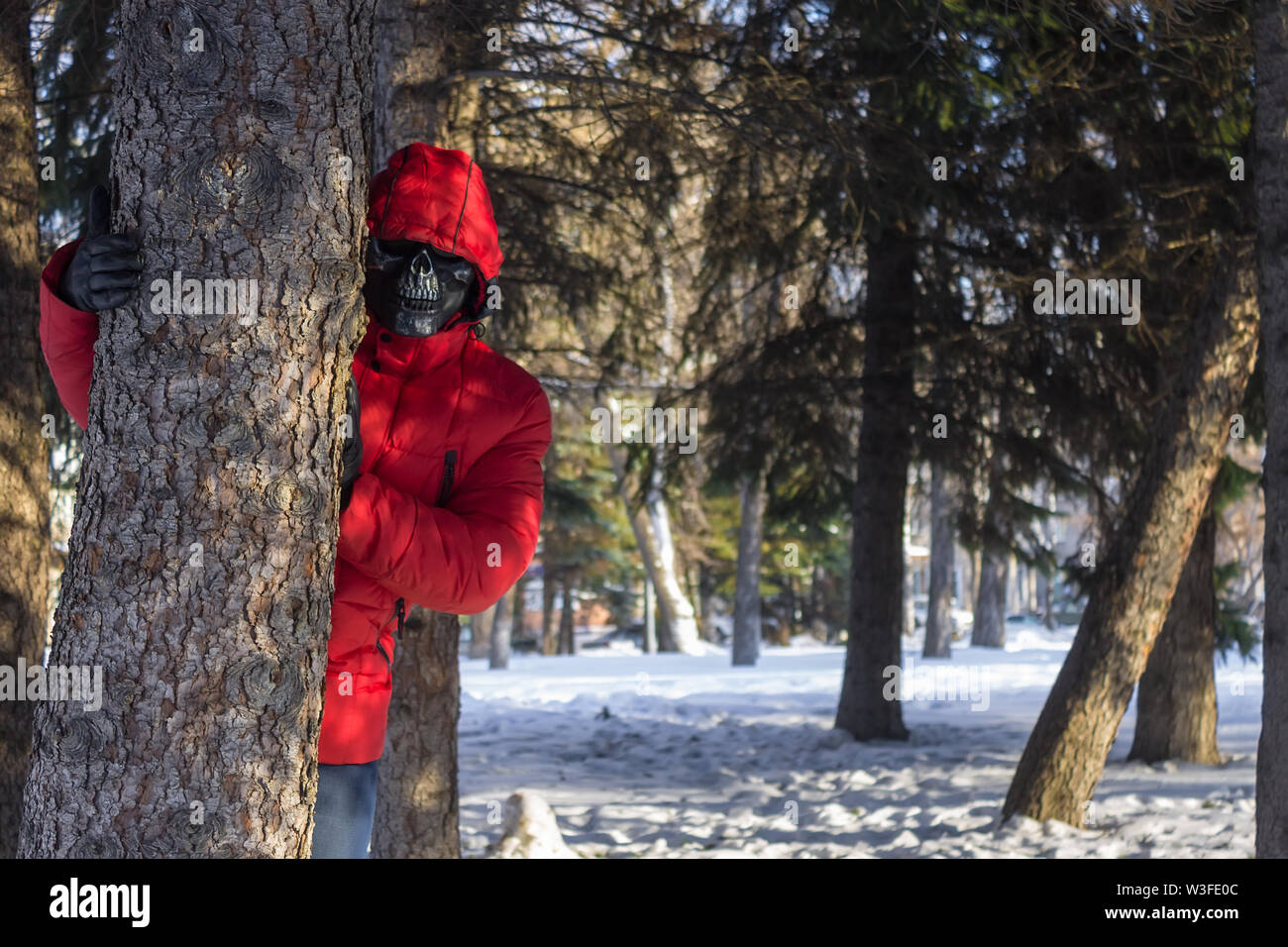 Brutal killer in a scary mask is waiting for his victim in the park - Stock Image