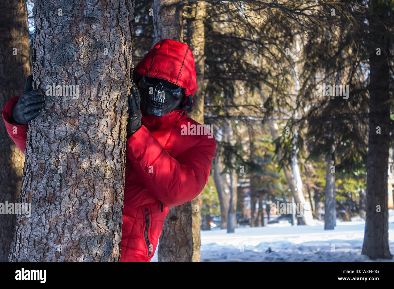 The terrible killer in the mask is waiting for his victim in the park - Stock Image