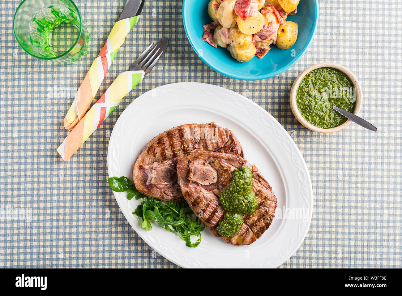 Chargrilled British Lamb leg steaks with chimichurri sauce and potato salad, overhead on chequered table cloth Stock Photo