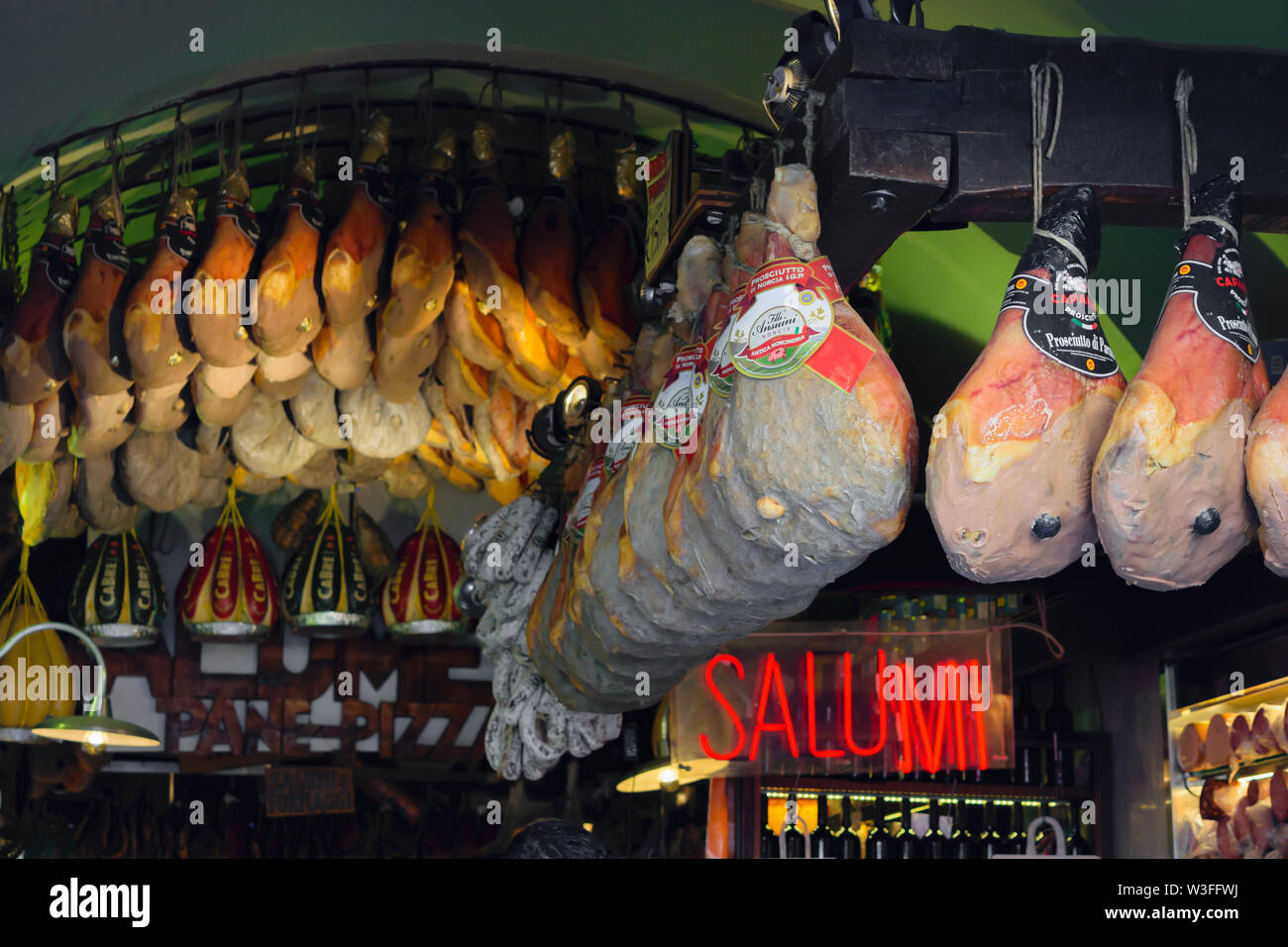 Rome, Italy 19 JUN 2019 Various types of huge smoked hams hanging in local meat shop where sells various type of salami sausages, smoked hams and wine - Stock Image