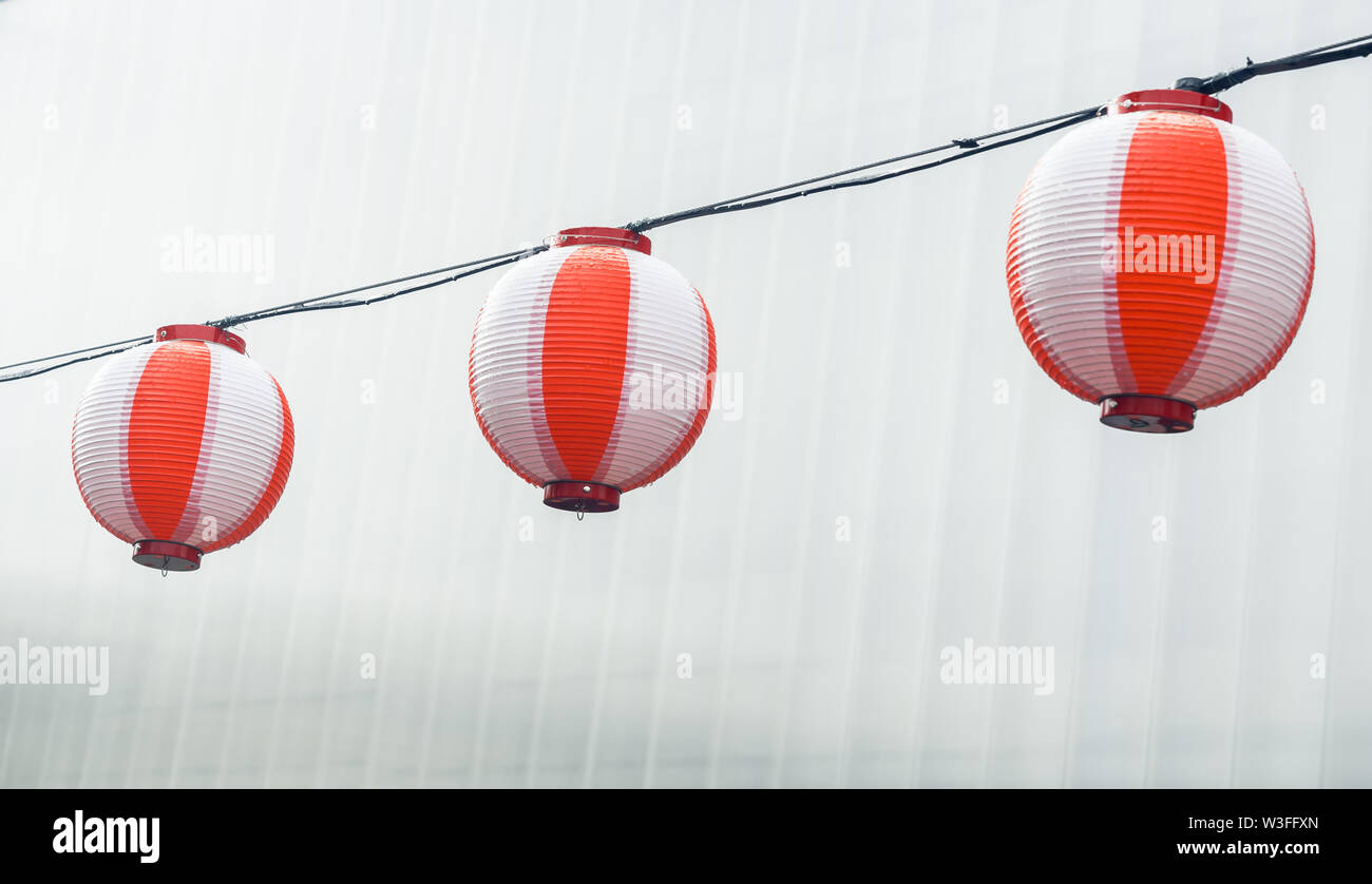 Three round paper red-white japanese lanterns Chochin hanging on garland sky background - Stock Image