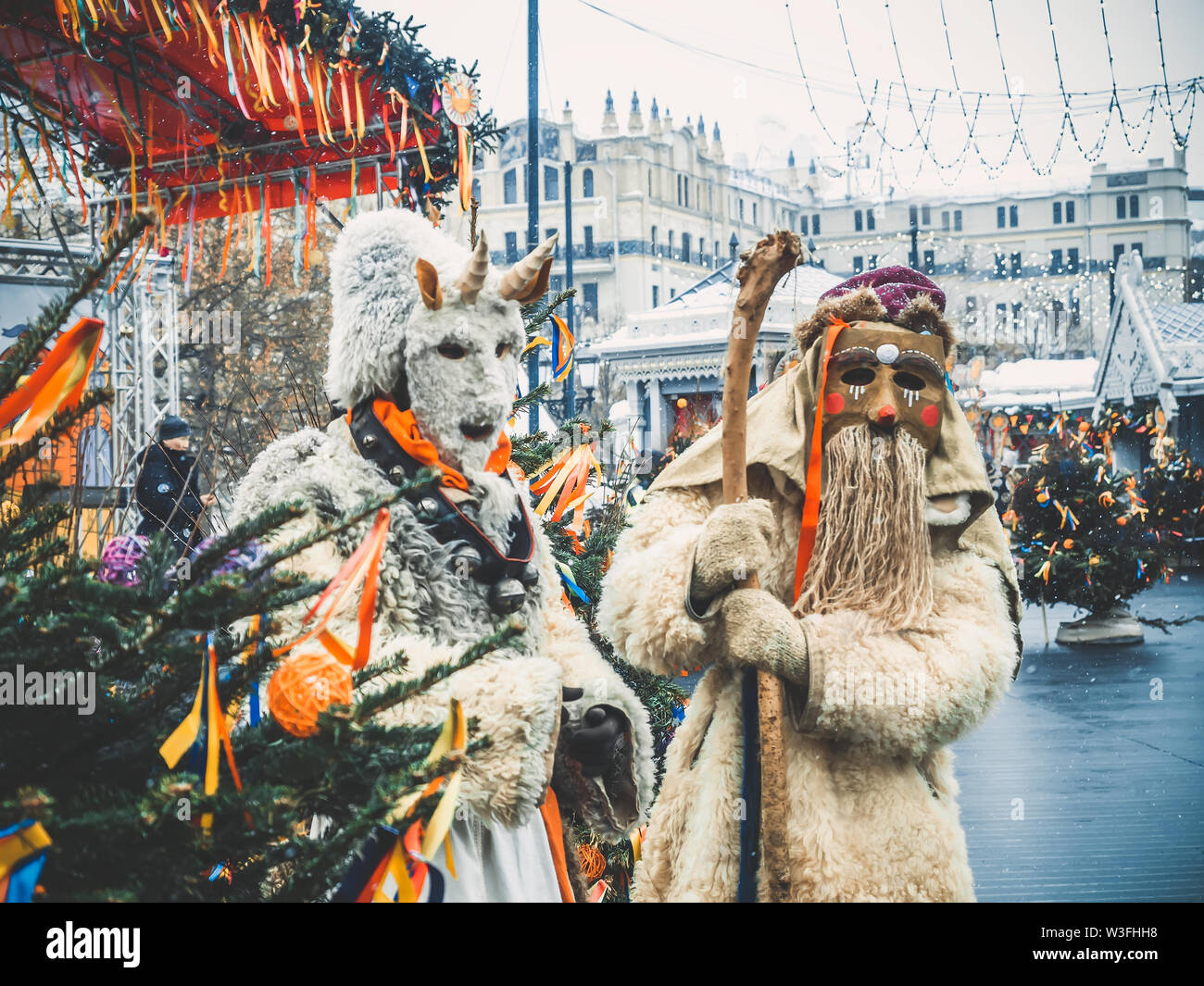 MOSCOW, RUSSIA- FEBRUARY 2017: The mummers walk the streets and entertain the people. Disguised in the wood goblin and devil, the actors play the role - Stock Image