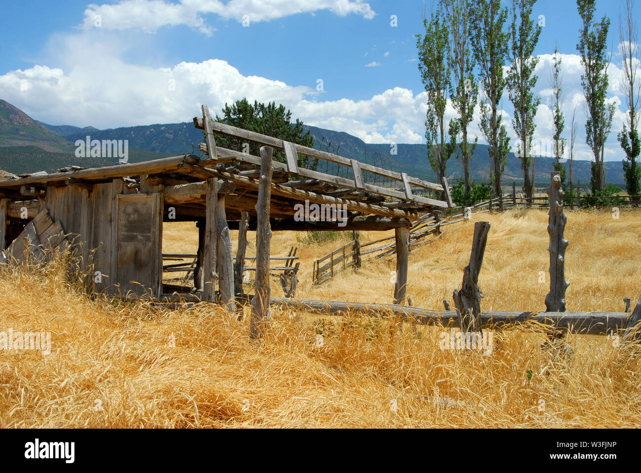 Southwestern landscape of ruins of an old abandoned ranch with stables and dry grass framed in by the mountains - Stock Image