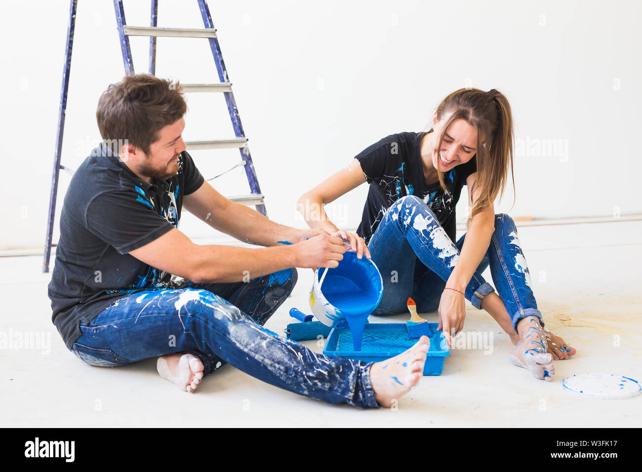 Repair, renovation and people concept - couple going to paint the wall, they are preparing the color and brushes. - Stock Image