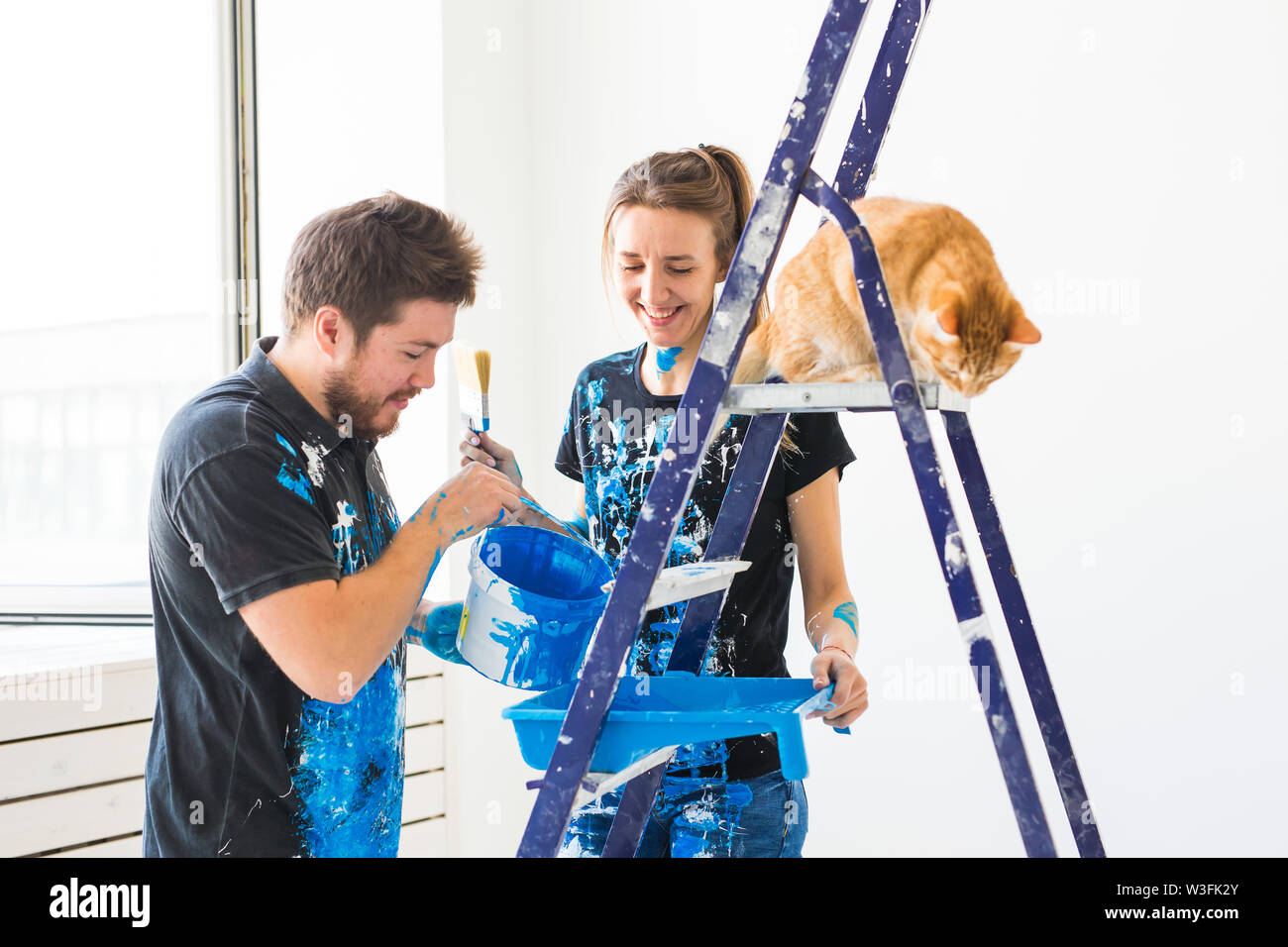 People, renovation and repair concept - portrait of happy couple with cat pour paint. - Stock Image