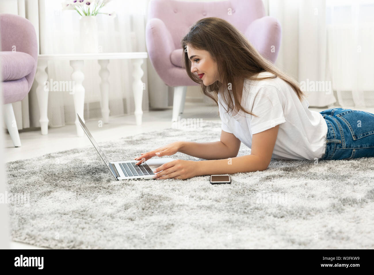 attractive young brunette woman wearing jeans and white t-shirt lying on the floor in bright livingroom with her laptop and smartphone - Stock Image