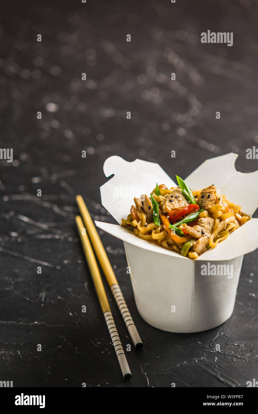 Chinese noodles in a box with chicken and vegetables with sticks. Wok food delivery from restaurant on dark background from side view. - Stock Image