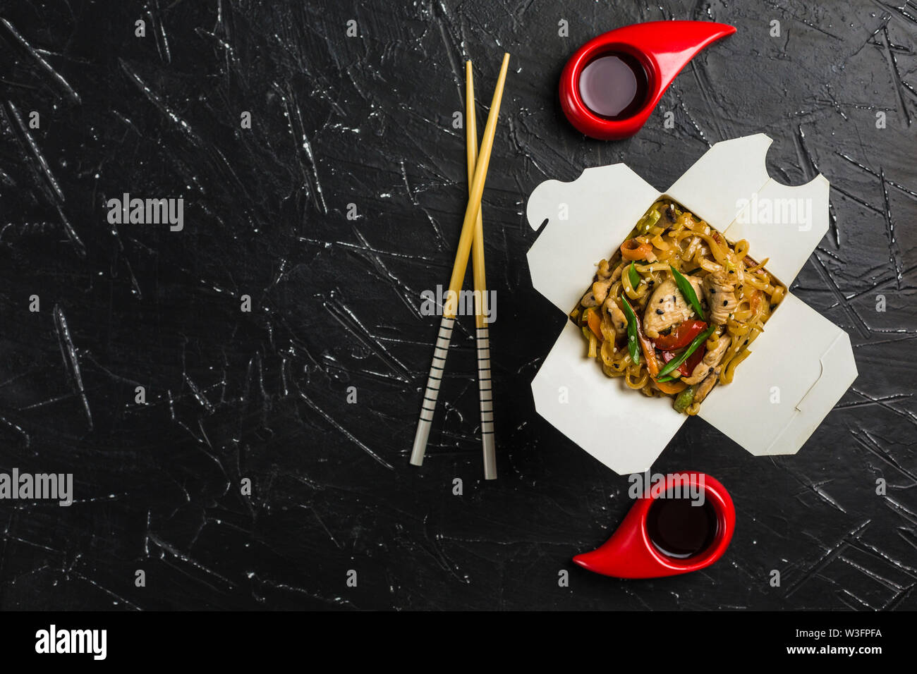 Chinese noodles in a box with chicken and vegetables with sticks. Wok food delivery from restaurant on dark background from top view. - Stock Image