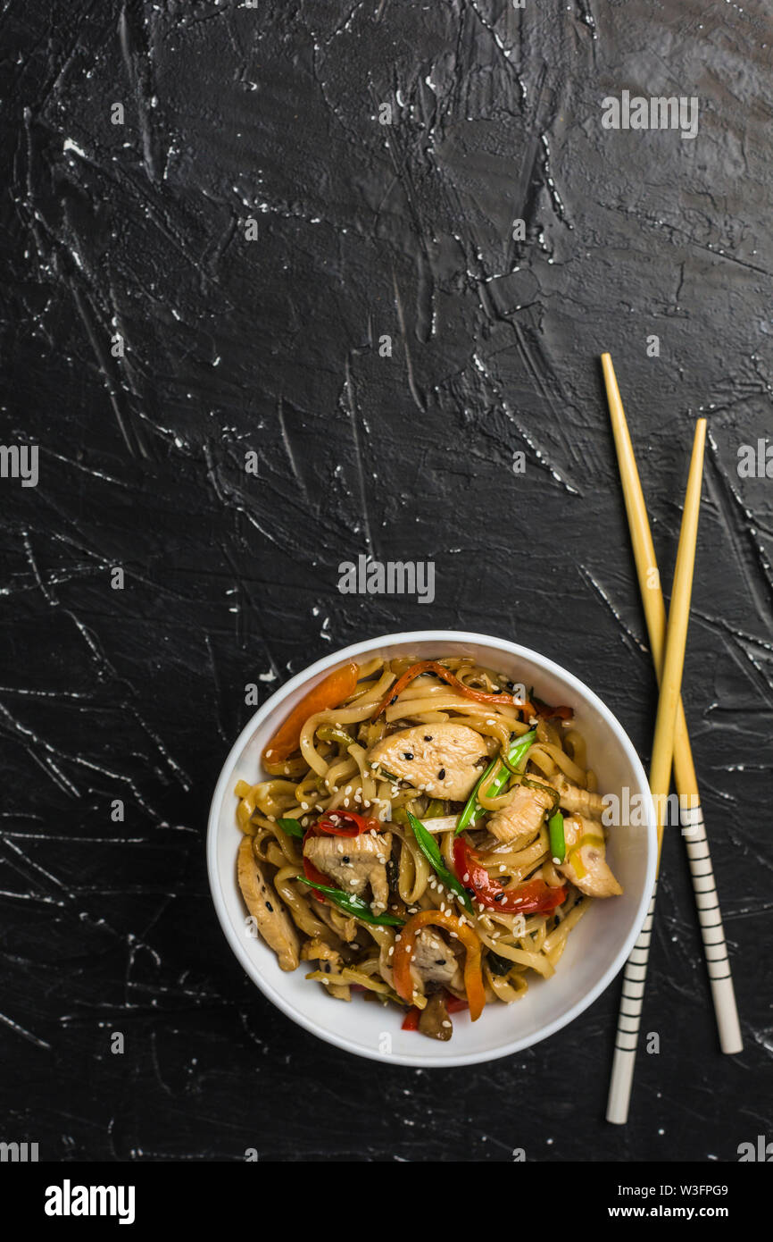 Chinese noodles in a Cup with chicken and vegetables with sticks. Wok food from the restaurant on a dark background from a top view. - Stock Image