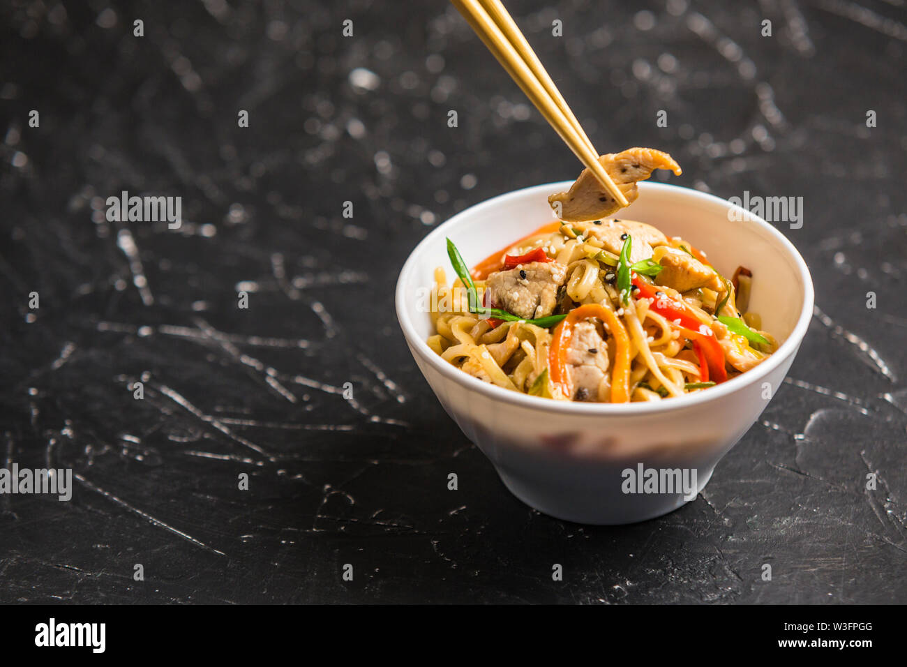 Chinese noodles in a Cup with chicken and vegetables with sticks. Wok food from the restaurant on a dark background from a side view. - Stock Image