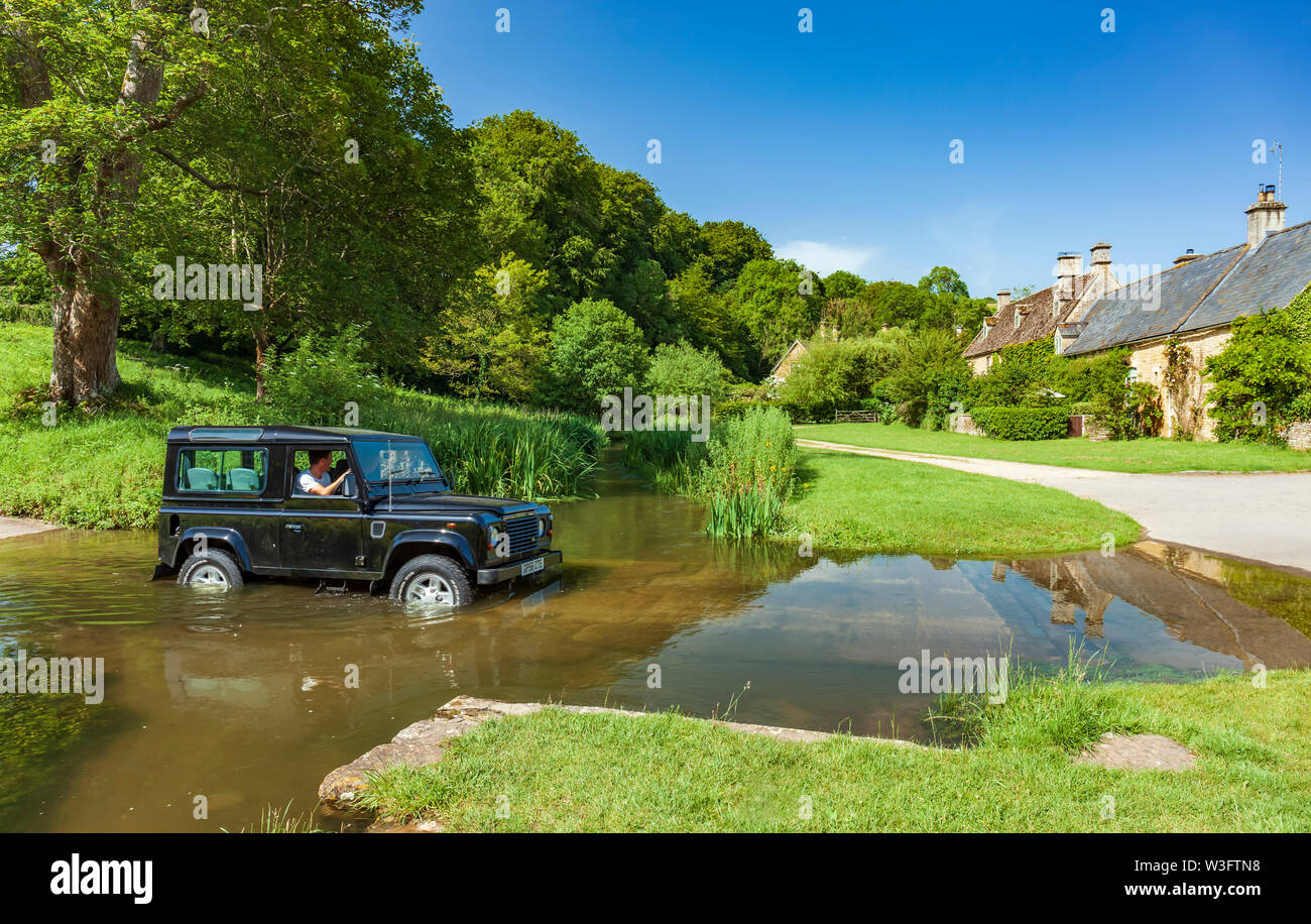 Land Rover Defender crossing the river Eye at a fording point. Upper Slaughter, Cotswolds,  Gloucestershire, England, UK. - Stock Image