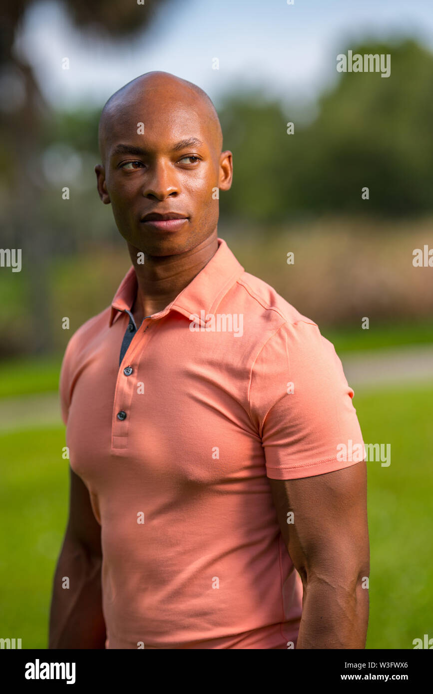 Portrait of a handsome African American bald man wearing a pink polo shirt - Stock Image