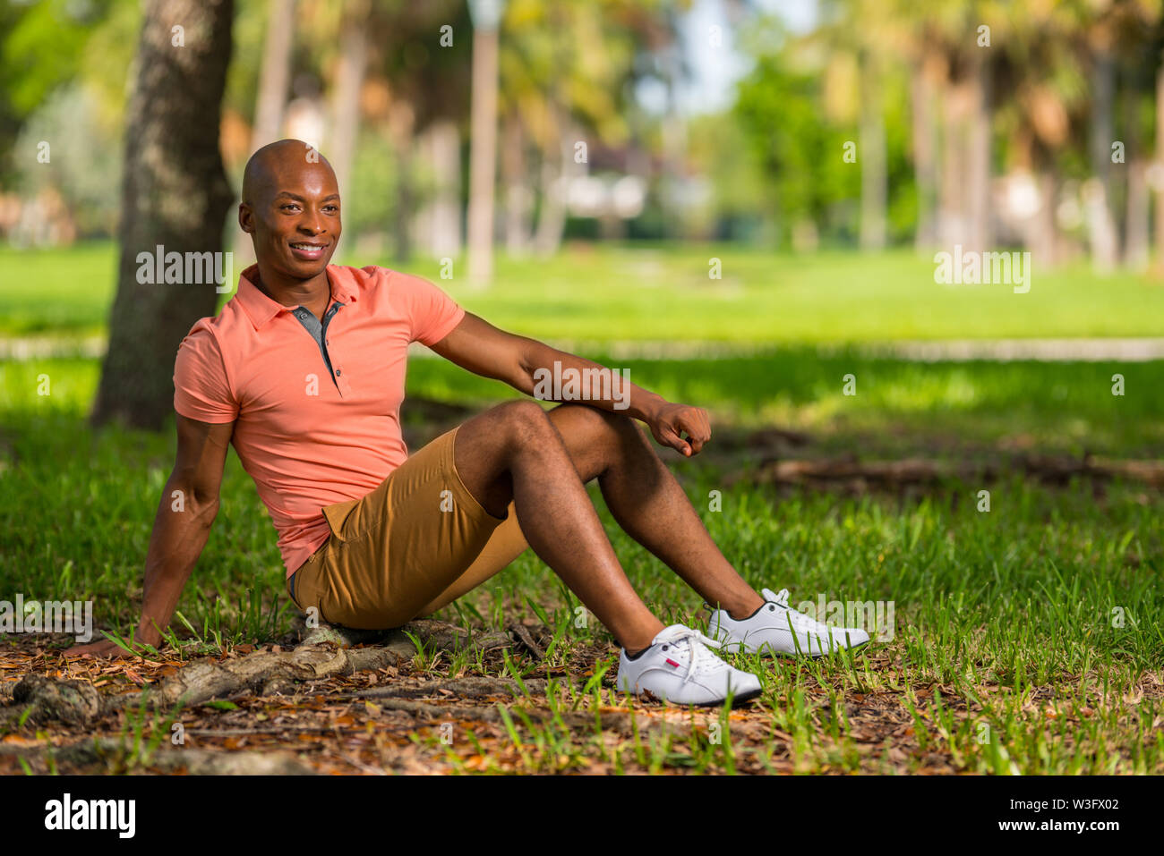 Photo of a young black man sitting in the park. Person wearing casual pink polo shirt and shorts - Stock Image