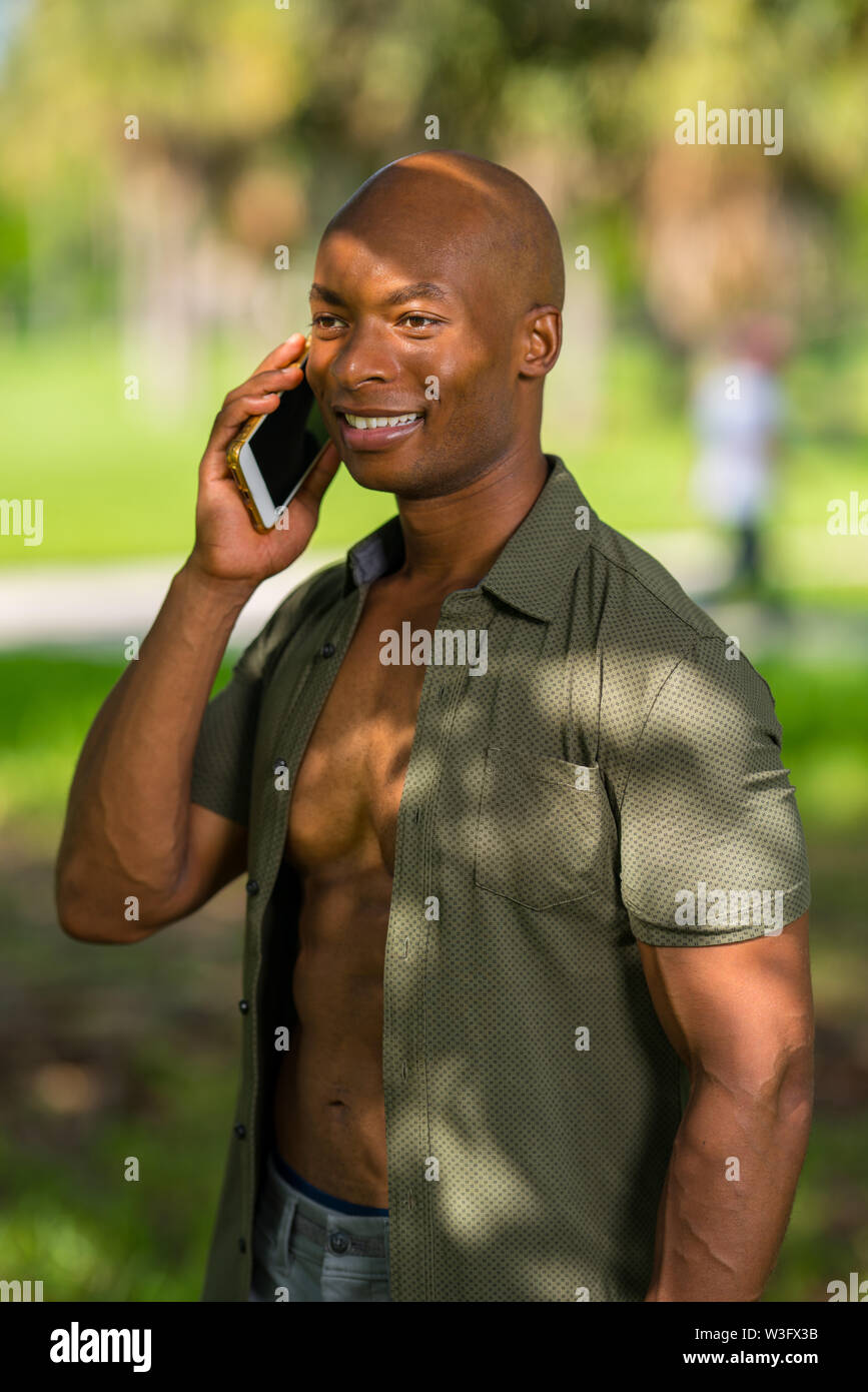 Portrait of a happy African American man talking on the phone outdoors in a park setting - Stock Image
