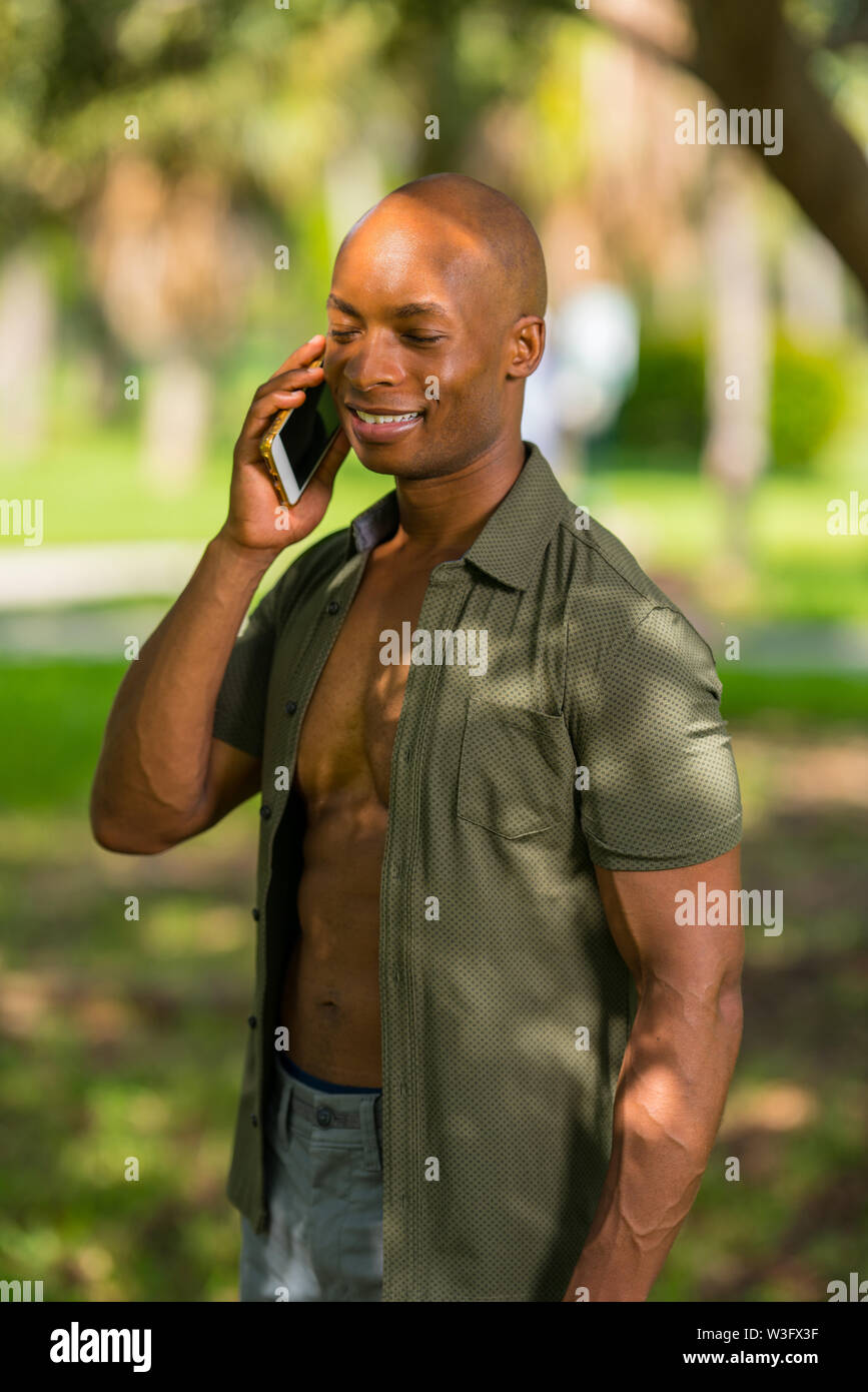 Image of a handsome black man talking on the phone. Male is smiling with eyes shut sun shining on face - Stock Image