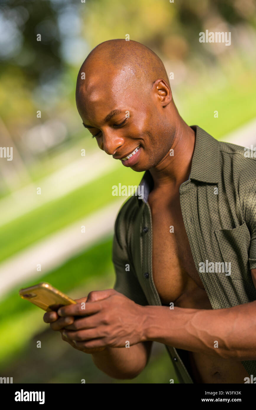Portrait of a handsome young African American man smiling and sending a text message on his smartphone - Stock Image