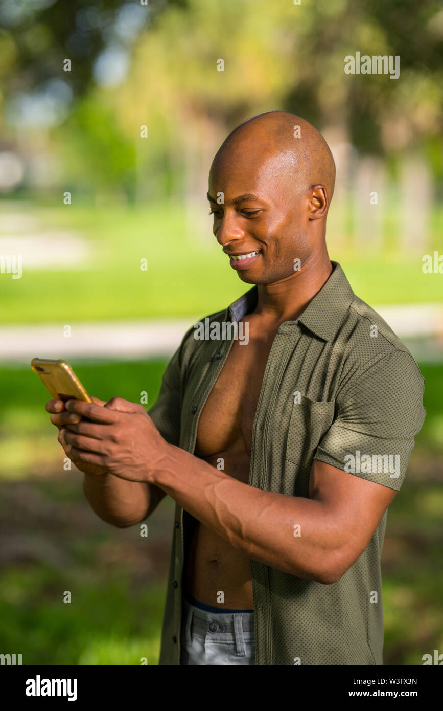 Photo of a handsome black man sending a text message on his smartphone - Stock Image