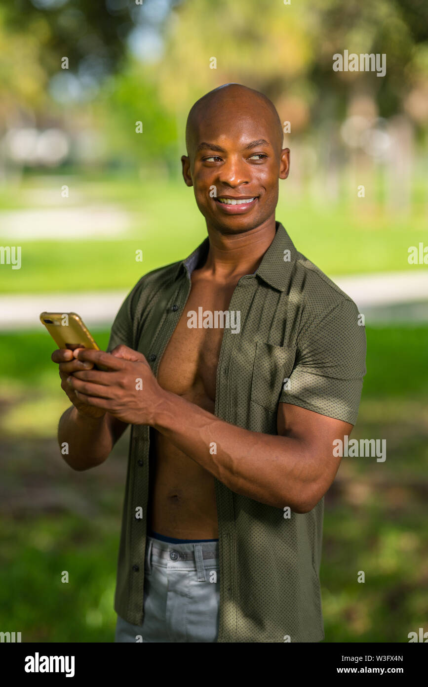 Handsome man sending a text on his smartphone and glancing over his shoulder - Stock Image