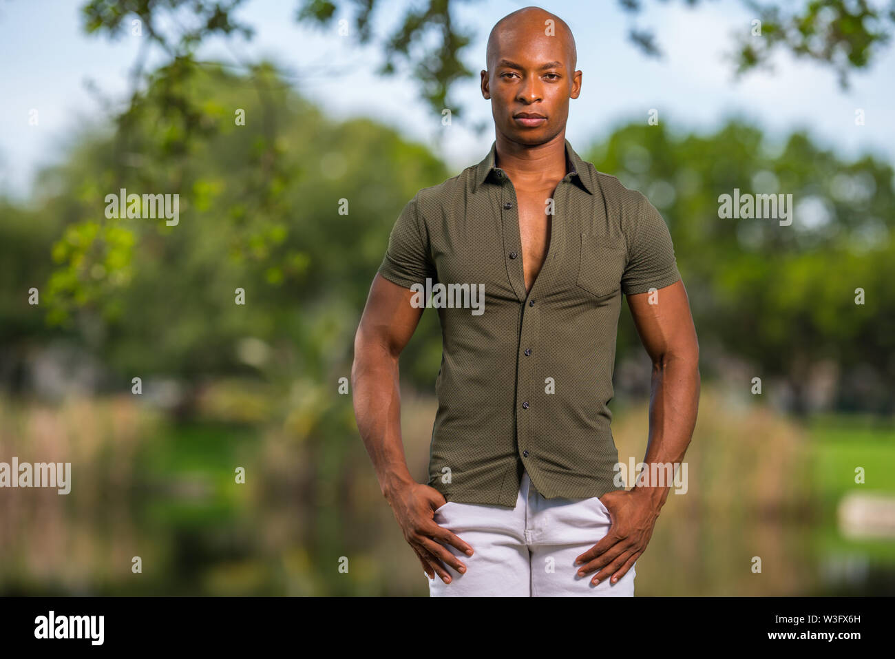 Photo of a handsome young African American male model posing with hands in pockets - Stock Image