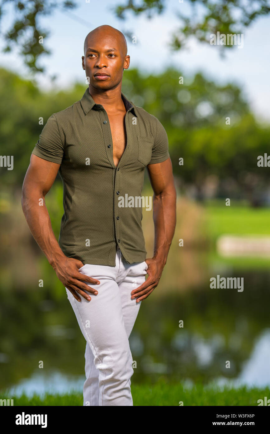 Photo of a handsome man posing with hands in pockets at a park setting - Stock Image