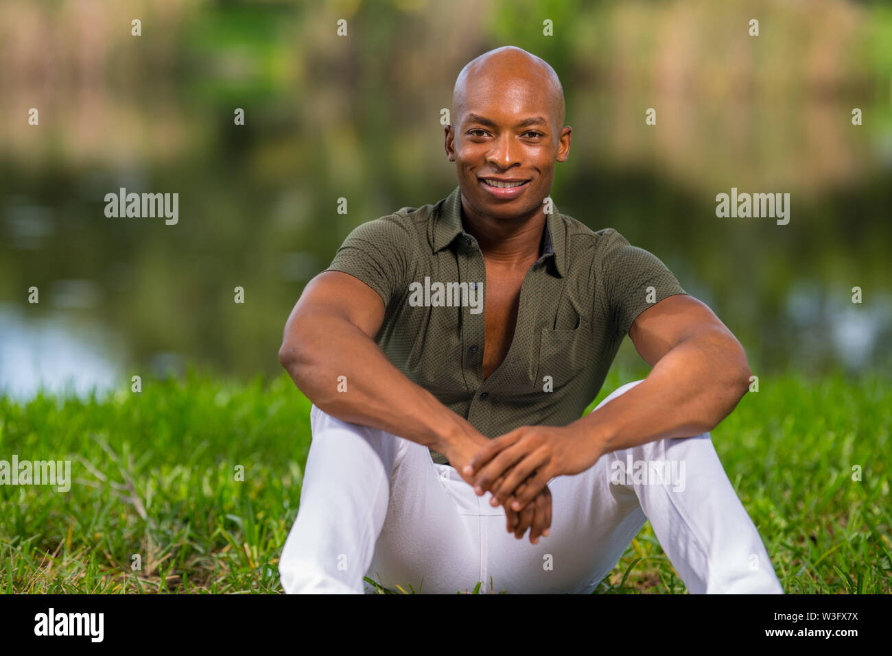 Portrait of a fashionable African American man sitting on grass in the park. Man is smiling and looking at camera - Stock Image