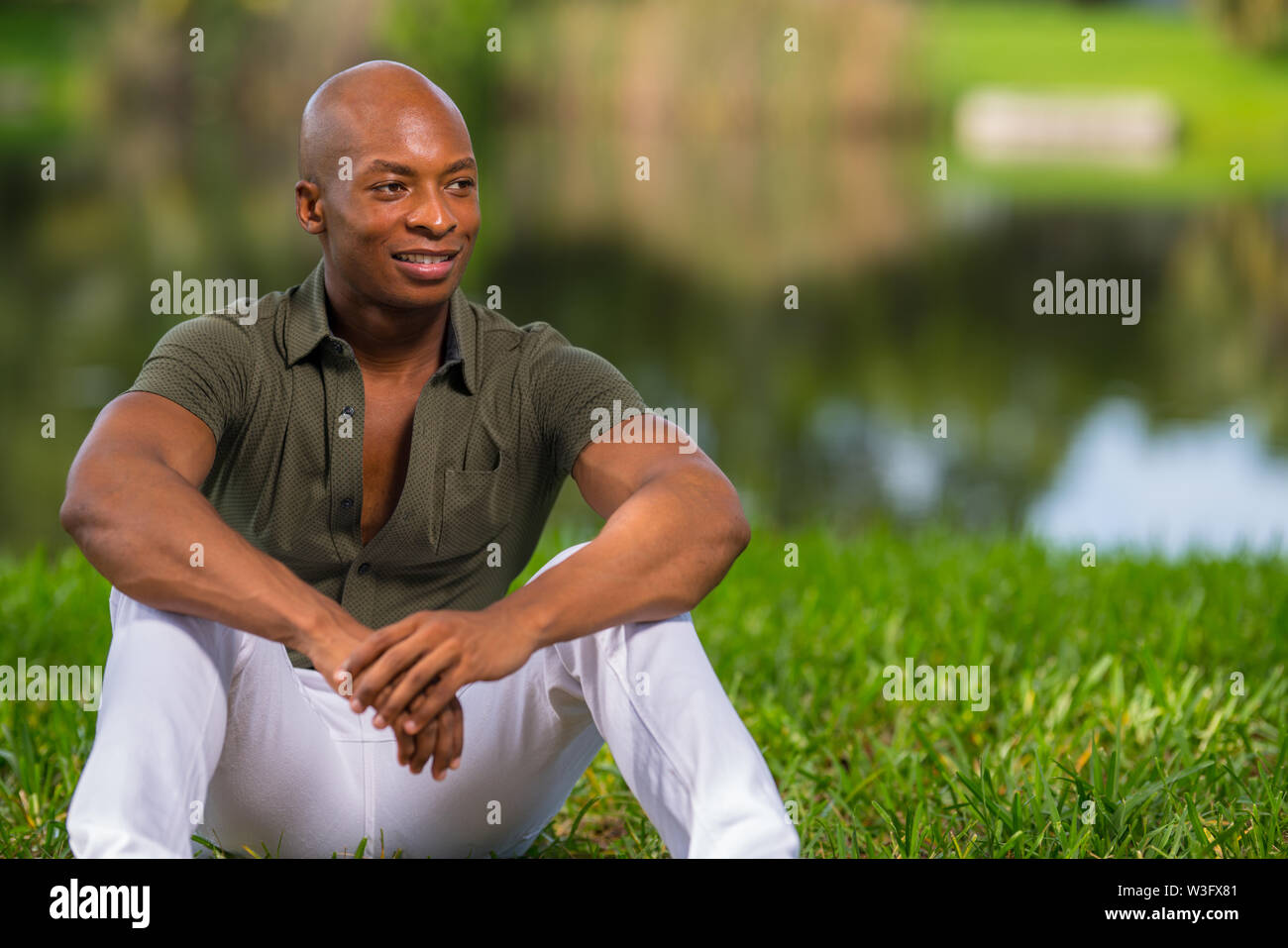 Portrait of a fashionable African American man sitting on grass in the park. Man is smiling and glancing of camera - Stock Image