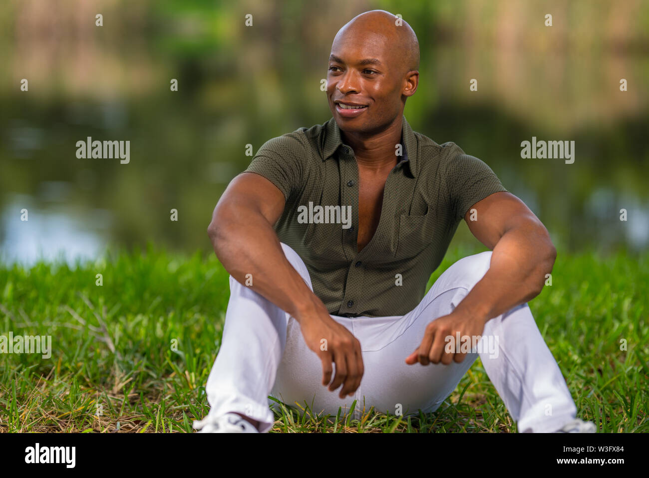 Portrait of a fashionable African American man sitting on grass in the park. Man is smiling and looking to his right - Stock Image