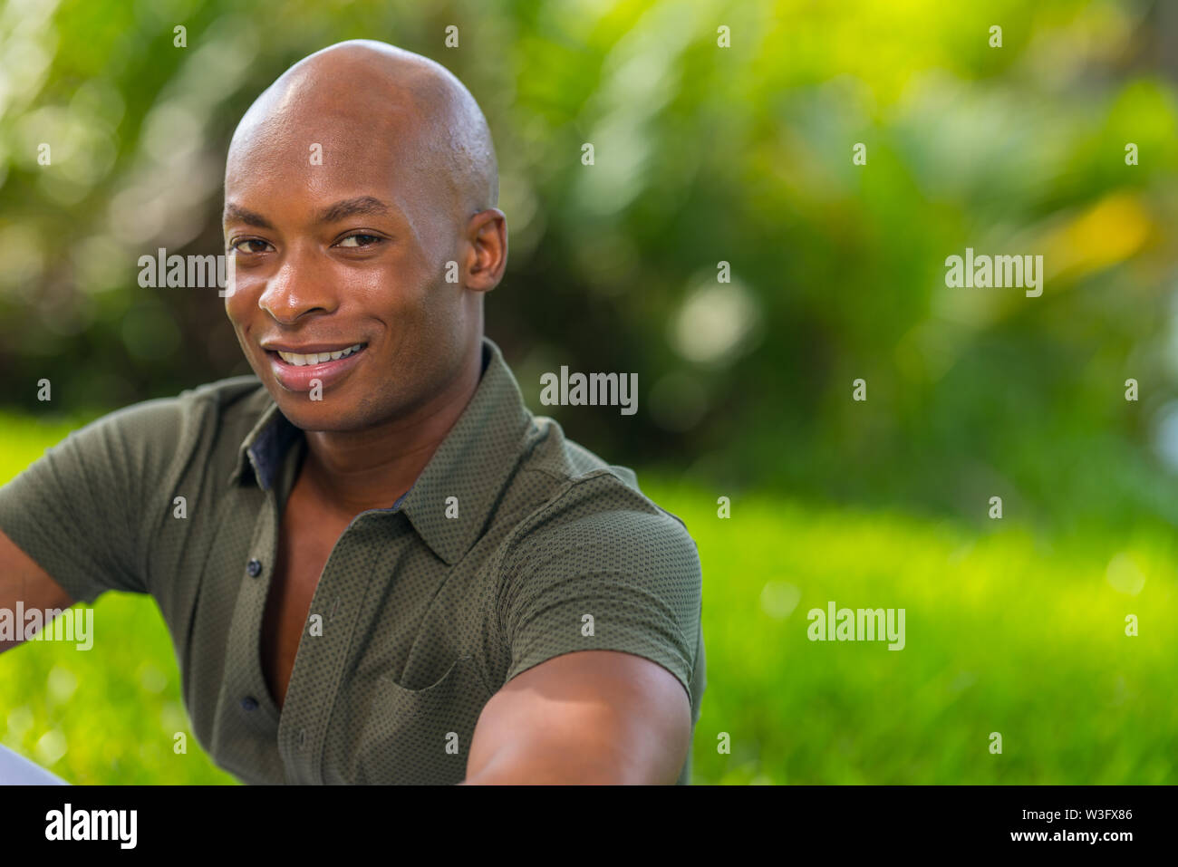 Vibrant portrait of a handsome young African American man smiling at the camera. Man is posing outdoors in a park setting - Stock Image