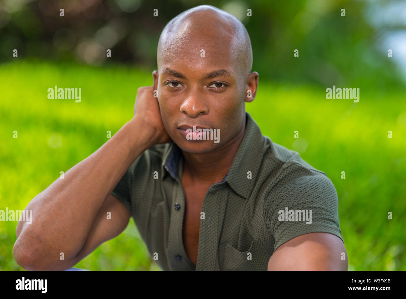Photo of a handsome man looking at the camera with head resting on his hand. Vibrant green colorful background in the park - Stock Image