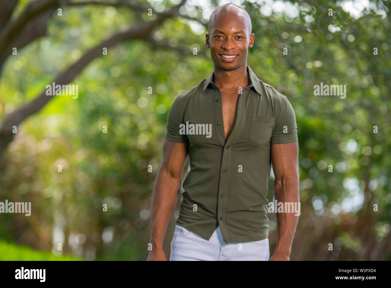 Handsome man posing in stylish clothing at a park scene in summer - Stock Image