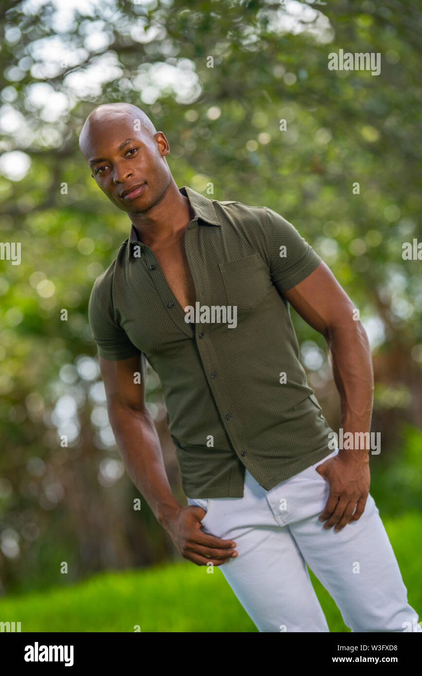 Handsome male model posing in the Park. Portrait of African American guy in casual clothing and thumbs in pockets - Stock Image