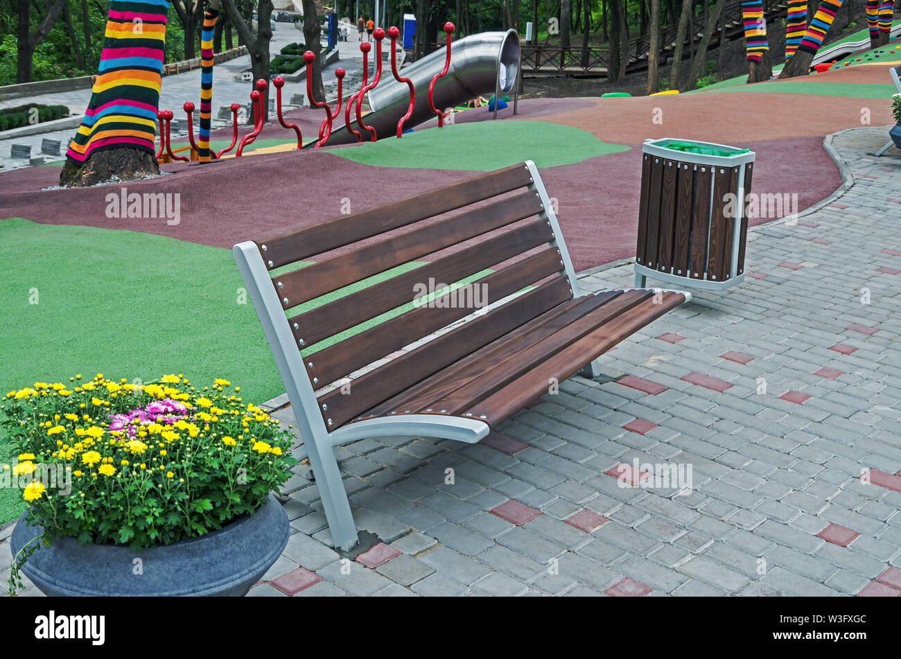 Recreation area with bench, a flower pot and trash can at playground in the city park - Stock Image