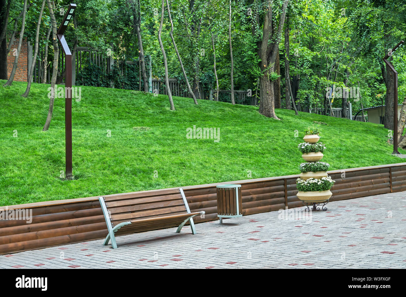 Recreation area with bench, a flower pot and trash can in the old city park - Stock Image