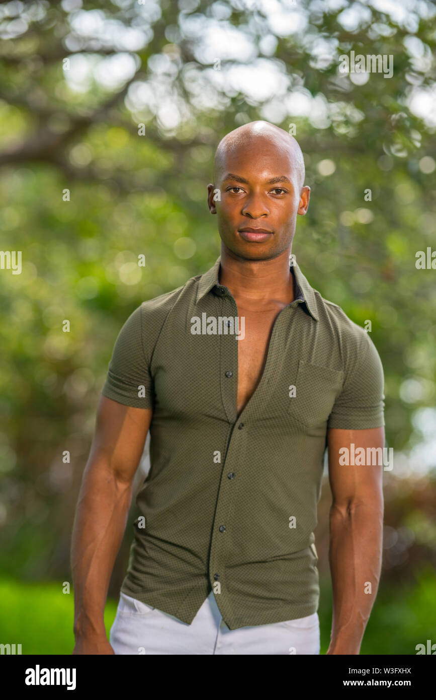 Portrait of a handsome African American male model posing in a vintage retro shirt at a park setting summer - Stock Image