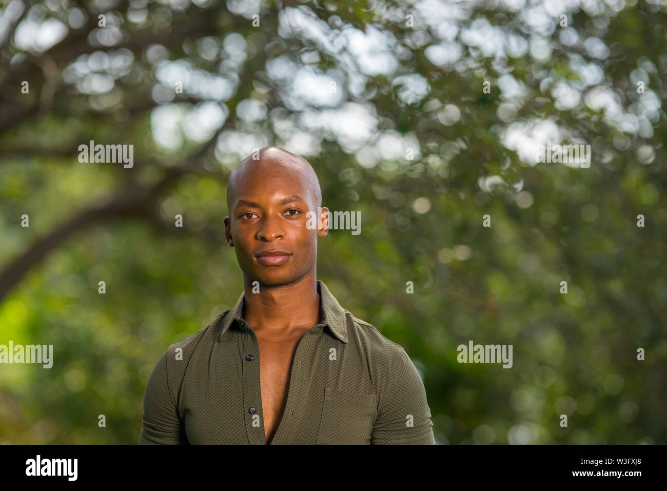 Headshot portrait of a handsome African American or Jamaican male model posing at a park scene - Stock Image
