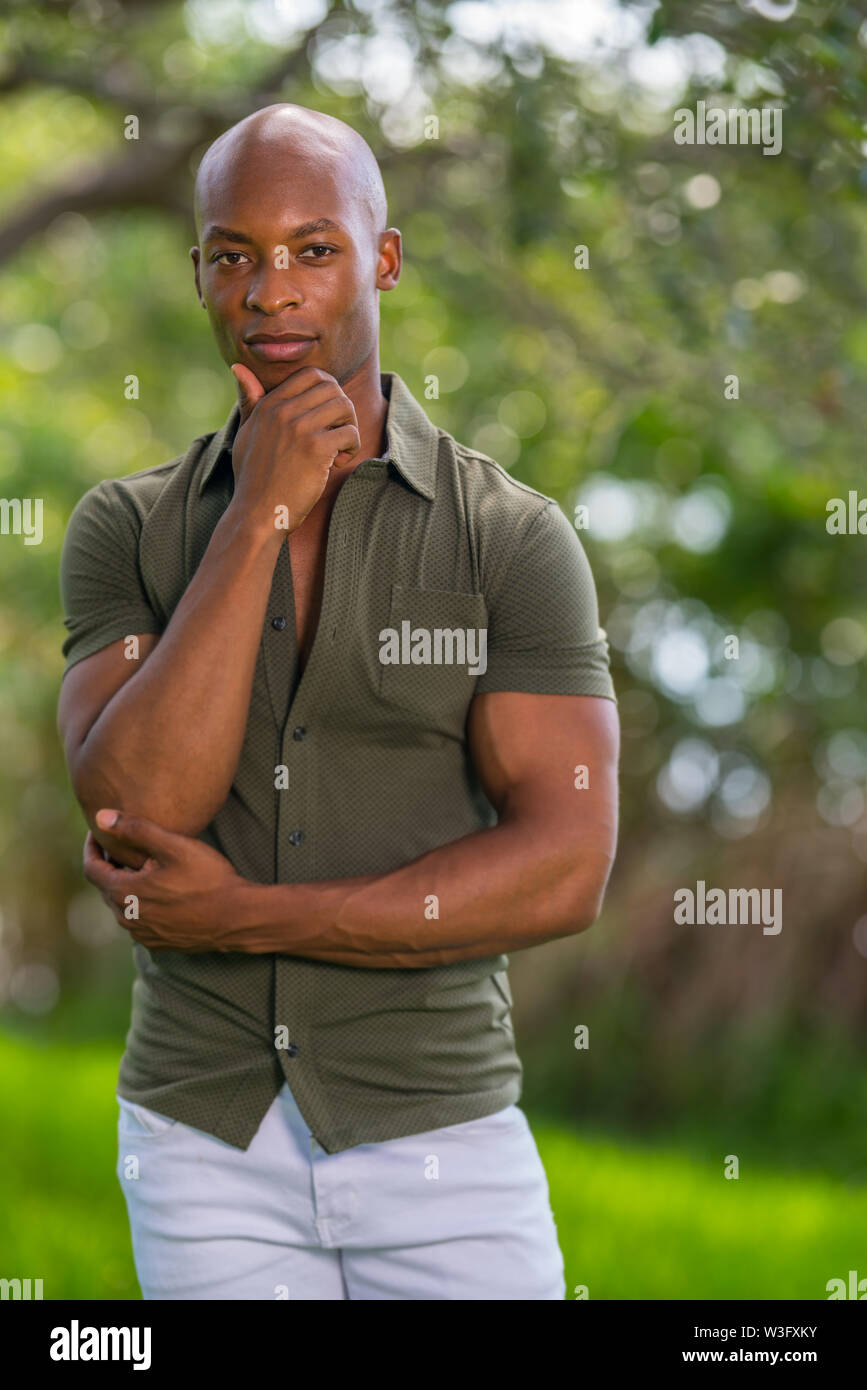 Portrait of a handsome black model posing with hand under chin. Image taken at a park scene - Stock Image